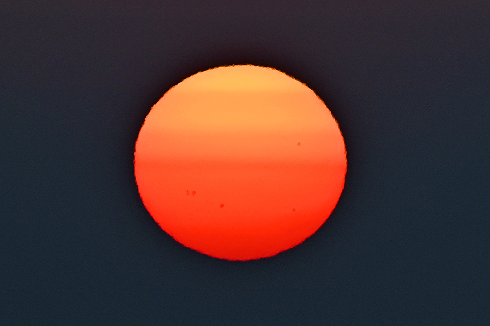 Closeup picture of the sun during a sunset, some sun spots visible