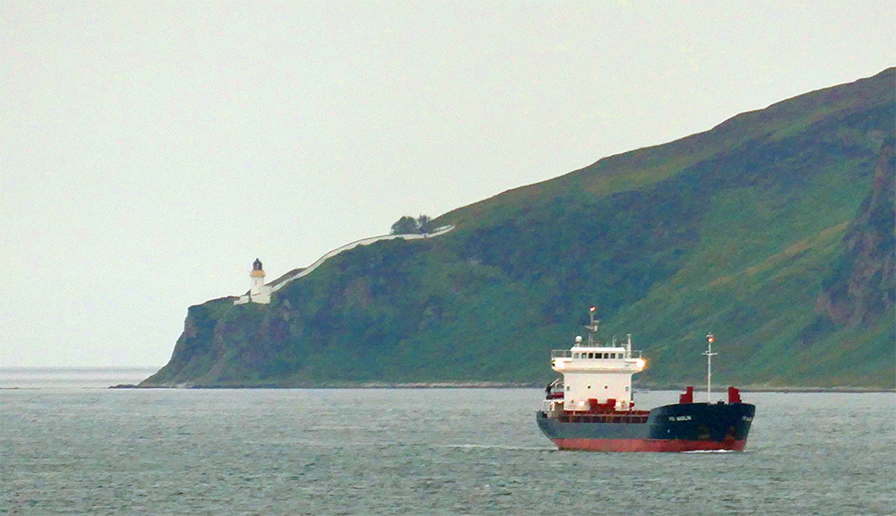 Picture of a small freighter passing a lighthouse on top of cliffs