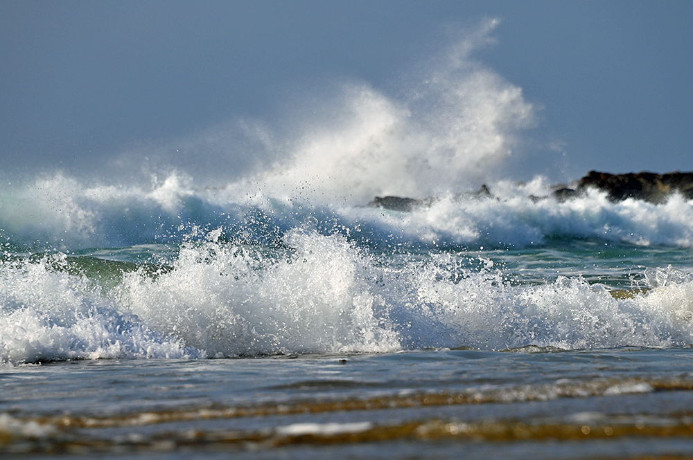 Picture of waves in various sizes rolling into a bay and breaking on the rocks and beach