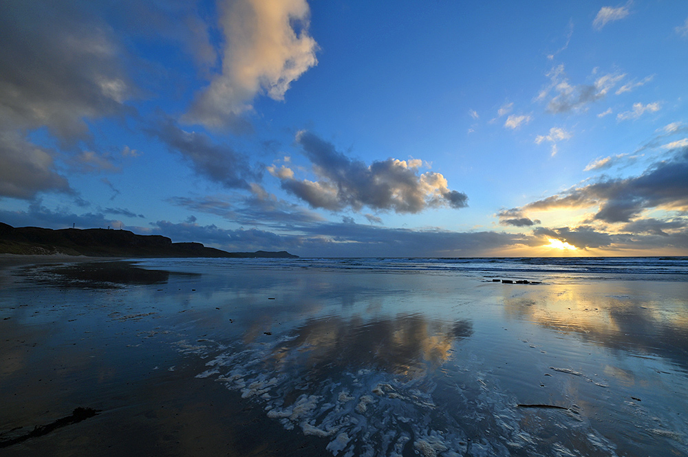 Picture of clouds reflecting on a wet sandy beach at sunset